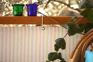 Stoffet er festet til rekkverket med snorstrikk som er trædd gjennom maljer oppe og nede.