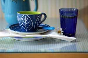 Et gammelt bord med merker og riper i platen, ble raskt og rimelig fornyet med en bit stoff og en glassplate.