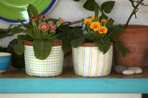 Hyllen er malt i en frisk turkisfarge, og blomsterpottene har fått skjulere av reststoff.