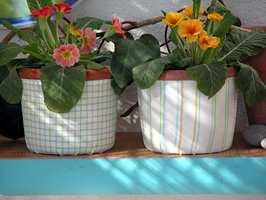 De minste stoffrestene ble akkurat nok til å kle et par blomsterpotter. To til tre strøk med decopagelim beskytter stoffet mot smuss og vannsøl.