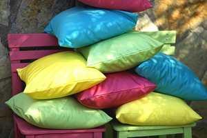 Vi har sydd puter med ulike farger valgt ut fra fargene på stripene i duken.