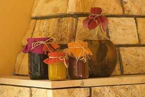 Urteoljer, krydderglass og krukker fikk dekorative hetter av stoffrestene. Bruk en asjett som mal og knytt en hyssing eller bastsløyfe rundt stoffet.