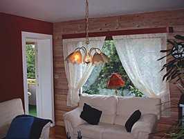 Før: En gammeldags stue med furupanel og mørke farger.