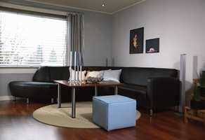 Stuen etter: Kalde vegger, blankt stål og sort hud gir et maskulint preg.  Kombinasjonen av transparente gardiner og det varme gulvet myker opp.