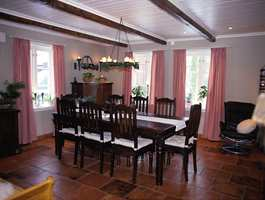 Gjennomført bruk av terrakottafargete fliser og takbjelker også i stuen. Gardinene har country-stil.