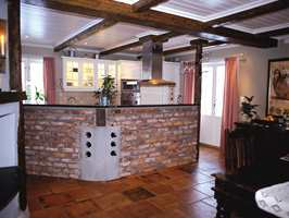 Fra den åpne stueløsningen mot kjøkkenet: keramiske fliser, teglestein og beisede bjelker.