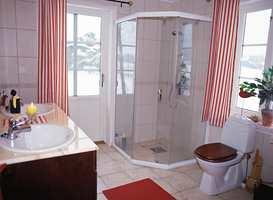 Sotre vindusflater og lyse fliser har gjort badet lyst.