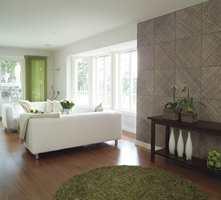 Lyse vegger og lyse, lave møbler skaper luftighet og romfølelse. Veggfeltet kledd med bambus trer frem som effektfull kontrast mot det lyse.