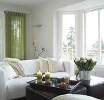 En frisk og frodig vårgrønn nyanse bringer naturfølelse inn i den bleke fargeskalaen. To puffer er brukt som bord mellom sofaene.