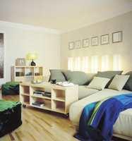 STUA ETTER: Velkommen til vennefest! Gulv og vegger er nøytrale og møblene kan lett passe inn i andre leiligheter senere. Møblene er også lyse, det er pledd og sofaputer som gir farger til rommet. Sofaen, som er en sovesofa, skulle være stor og komfortabel for der skal hun og vennene slenge seg ned foran fjernsynet.  Lampene bak sofaen er både funksjonelle og dekorative og lett flyttbare hvis man ønsker å ominnrede. Dessuten tar disse lysskulpturene opp gjentagelsestemaet fra entreen hvor hver dør er lyssatt.
