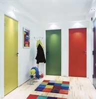 ENTREEN ETTER: Se så lyst og trivelig det ble! Interiørarkitekten har valgt glade farger på tepper, bilde og dører. Entreen har plutselig fått et ungdommelig preg som også hadde passet fint inn i leiligheten til en barnefamilie. Legg merke til lyslistene i taket – en spot over hver dør. Spotene markerer dørene, gir lys til rommet og bidrar til å gi et større fargespill. - De trodde jeg var gal da jeg lanserte ideen med en farge for hver dør, men etterpå mente de det var veldig sprekt! sier Wenche Aurland.