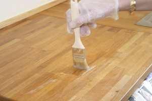 Påfør maling- og lakkfjerner i et tykt lag over hele benkeplaten med en pensel.