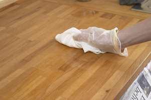 Dypp og kryst stålull nr. 0 i en skål med møbelrens og vask flaten med lett hånd. Deretter
