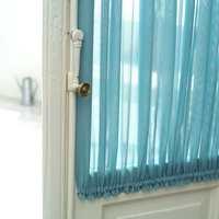 Den turkise fargen er et diskré gjennomgangstema i hele leiligheten. Her har døren mellom hagestuen og soverommet fått enkle, men effektfulle gardiner.