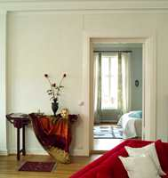 En knallrød sofa har blitt det nye midtpunktet i storstua. Sofaen er en virkningsfull bindeledd mellom det mørke spisestuemøblementet og de lyse veggene.