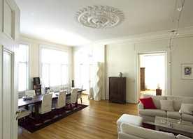 To lyse sofaer og et salongbord i lyst treverk dominerte den ene halvdelen av stuen. Kontrasten mellom den lyse sofakroken og det mørke spisestuemøblementet ga rommet et ubalansert uttrykk.