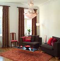 Øisteins rom: Den innerste stuen fikk et varmere uttrykk ved hjelp av tykke, klassiske gardiner, fyldige, mørkebrune modulstoler og et rufsete oransje teppe. Puter i varmrosa og lilla setter et feminint preg på leilighetens nye