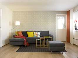 Den ene kortveggen i stuen er møblert med ny grå sofa med sjeselongdel og frittstående pall (Milano fra Bolia). Sofaen er fylt med puter i friske farger og mønster (Hilmers Hus). Det store lappeteppet er sydd sammen av ulike mønster i silke. Veggen bak sofaen er tapetsert med en retro tapet i gråtoner (Ecco Fond 05 5922 fra Borge). Settbordene (Nesting tables) er designet i 1926 av Josef Albers for Vitra. Bordene har ben av eik og med topplate av farget akrylglass.