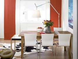 Spisebordet er plassert like ved åpningen inn mot kjøkkenet. I enden av bordet står det høyeste av settbordene, som også blir brukt som avstillingsbord. De hvite formbøyde stolene har stålben. Både spisebord og stoler kommer fra Bolia. På gulvet ligger et kuskinn i sort og hvitt fra Gulvex.