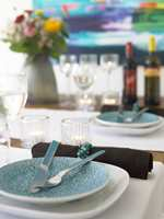 Bordet er dekket til fest. Turkis dekketallerkener på løpere i lysblå lin med brune servietter til (Hilmers Hus). Serviettringer av turkis perler og en vakker sommerbukett pynter opp.