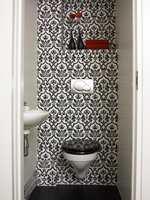 På det lille toalettet er det valgt et dristig utrykk. Stormønstret sort og hvit tapet, sort lokk på veggskålen og sort vinylgulv. Sideveggene er malt hvite. I det ene hjørne har det akkurat blitt plass til en liten vask.