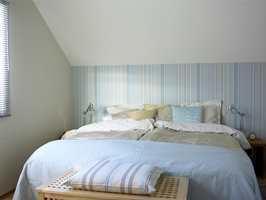 Foreldresoverommet har fått en skikkelig ansiktsløftning. Veggen bak sengen er tapetsert med en stripete tapet i blåtoner og beige (TJ 46222 Taj Mahal, Borge). Resten av veggene er malt i NCS 1005-Y30R, som er en varm beige farge. Sengen er redd opp med sengetøy fra Turiform, Nordisk Fjær. Mange puter i beige og lysblått harmonerer med sengeteppe (Linnum, Hilmers Hus). I enden av sengen står en oppbevaringskiste i bjerk, som også er fin å sitte på når strømper og sokker skal på plass.