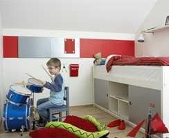 Fredriks rom er ikke stort, men det er lagt vekt på å ha så mye gulvplass som mulig. Her slår han på sitt nye trommesett som alle kameratene synes er mega-kult. Foreldrene skulle kanskje ønske de hadde lydisolert rommet? Den halvhøye sengen har trappehylle i midten og oppbevaring på begge sider. Hyllene over sengen er de samme som ved hylleveggene. Fredriks høyeste ønske var å få et rødt rom. Det hadde vært litt voldsomt i dette lille rommet, men for å gi en følelse av rødt, ble det brukt i andre elementer. På kortveggen er det malt en rød stripe (NCS 1080 Y90R) som flukter med de 50 cm brede magnettavlene. Det røde sengetøyet kommer fra Turiform og postkassen fra Hilmers Hus. Foreldrene er flinke til å legge brev i postkassen, noe som blir satt stor pris på at Fredrik som sjekker den hver dag.