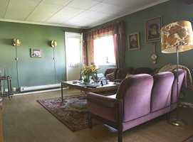 Mørke nyanser av grønt og vinrødt tynget stuen og fikk volumet til å krympe visuelt. Takplatene gjorde at rommet føltes enda mer lavloftet. Peisen virket ruvende, sammen med bueveggen og juksbjelken delte den opp rommet.