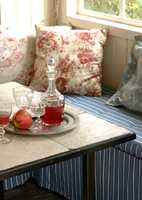 Bordet har plate kledd med rustikke, lyse fliser. En fin kontrast til husets skjøre, gamle glass som brukes til leskende saft på varme sommerettermiddager.