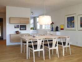 Nå er skyvedøren og deler av veggen til kjøkkenet fjernet for å gi bedre kontakt mellom de to rommene. Det er ryddet opp i kunsten, slik at bildene, blant annet av Lasse Kvernbo, fremheves. Vegghengt buffet gir et lett inntrykk. De nye møblene er i bøk som gulvet.
