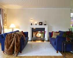 Den nye peisen i engelsk stil har fått møblering beregnet på peiskos og hyggelig samtale. Plexibordene tar ikke vekk utsikten til peisen. De blå sofaene sto før et annet sted i rommet.