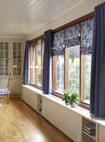 I dag skjuler spesialsnekrede hyller radiatorene. Og for å bryte opp den lange vindusveggen, har vinduene på midten fått dekorative liftgardiner.