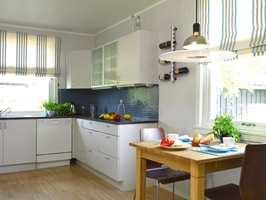 Kjøkkenet før og etter. Den kalde blåfargen gjorde kjøkkeninnredningen klumpete. Malt i samme farge som veggen ble den en del av rommet. Innredningen er beholdt, men modernisert med fjerning av lister og utskifting av den smårutete skapdørene. Benkeplaten i furu ble beiset mørk og lakkert. Blåfargen i de nye mosaikkflisene tas opp av fargene i gardinen.