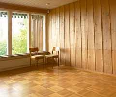 Stuen før og etter.  Da panelet i vegger og tak ble malt, forandret rommet karakter og ble lyst, luftig og tidsriktig. Det fine parkettgulvet kom nå til sin rett som kontrast til de malte flatene. Taket er malt blankt for å forsterke det luftige uttrykket og heve takhøyden.