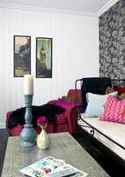 Sterke farger i turkis og rødt i møblene kombinert med hvitt, sort og sølv som rommets farger gir et friskt og kraftig inntrykk langt fra tradisjonell kjellerstueinnredning.
