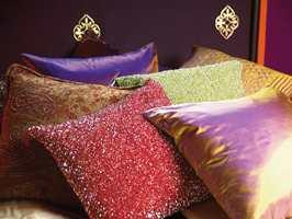 Det er ingen grunn til måtehold i dette interiøret, så sengen ble fylt med glitrende, fargerike og blanke puter.
