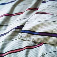 Delikat, blå- og hvitstripet sengetøy med kraftige kontraststriper på tvers.