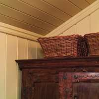 På et soverom med begrenset gulvplass, må man tenke i høyden. Her er to gode kurver til strømper og småting plassert oppå klesskapet.