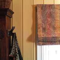 Liftgardinene i bomullsvelour er paisleymønstret. Fargene er varme og gir lunhet til rommet, og det tykke stoffet holder lyset ute når gardinen er trukket ned.