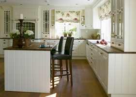 Kjøkkenet er kremfarget og innredningen er fra Drømmekjøkken. To barstoler i skinn står foran øya og er en velegnet plass for en rask frokost. Både benkeplaterog gulv er i kirsebærtre. Legg merke til det gøyale stoffet i liftgardinene. Fordi kjøkkenet er holdt i så rolige farger, kommer gardinene helt til sin rett.