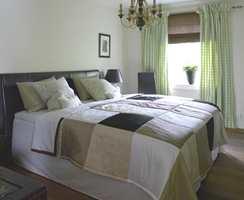 Foreldrenes soverom har sengegavl i skinn. Det flotte sengeteppet er sydd sammen av lapper i ulike kvaliteter som taft og chenille. De rutete gardinene hadde eierne fra før, mens liften er ny. Lysekronene understreker den klassiske og solide stilen.