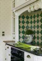 Nisjen over komfyren har diagonallagte fliser i grønt og hvitt. Disse fargene tas igjen i tekstiler i spisestuen.