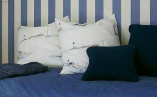 Detalj av sengen med jeans-sengeteppet og puter i samme tekstil som gardinen.