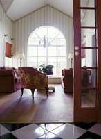 Det var disse røde sofaene i stuen innenfor hallen som var med på å bestemme rødfargen på veggene der. Stuen har stripet tapet i beige og krem, og det store buevinduet gir rommet lys og luft. Gulvet er i kirsebær, og taket er malt eggehvitt.