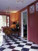 Hallen gir et gedigent første-inntrykk med sjakkmønstert marmorgulv og rødmalte vegger. Både glassdøren inn til stuen og døren til skyvedørsgarderoben er malt røde. Dette roer ned rommet. To prismekroner i taket understreker det elegante inntrykket.