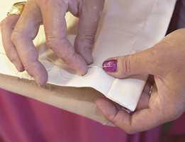 Sy innbrettet fast i hjørnet nederst på gardinet med hånd.