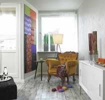 Glimt fra stuen hvor stoffcollage og varmgul stol luner rommet.