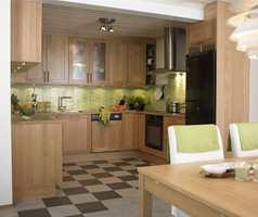 Et mye mer funksjonelt kjøkken med kjøkkenskap på tre vegger.