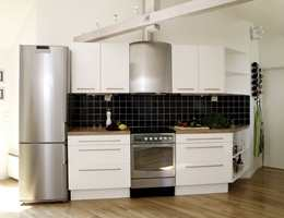 Kjøkkenet har skråtak og bjelker, og her er det valgt en moderne innredning som er flott kontrast i det rustikke rommet. Hvitevarer i stål og fliser over benken i svart glass er tøft og elegant i alt det hvite.