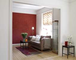 Fondveggen i denne stuen har fått rød tapet. Det myker opp i det ellers lyse interiøret og gir varme i rommet.  Rødt er på forskjellig måte brukt som kontrastfarge gjennom hele leiligheten og er med på å binde rommene sammen. Det buede, originale taket er tatt frem igjen og gir god romfølelse og fin lyseffekt. Takene ble malt matte.